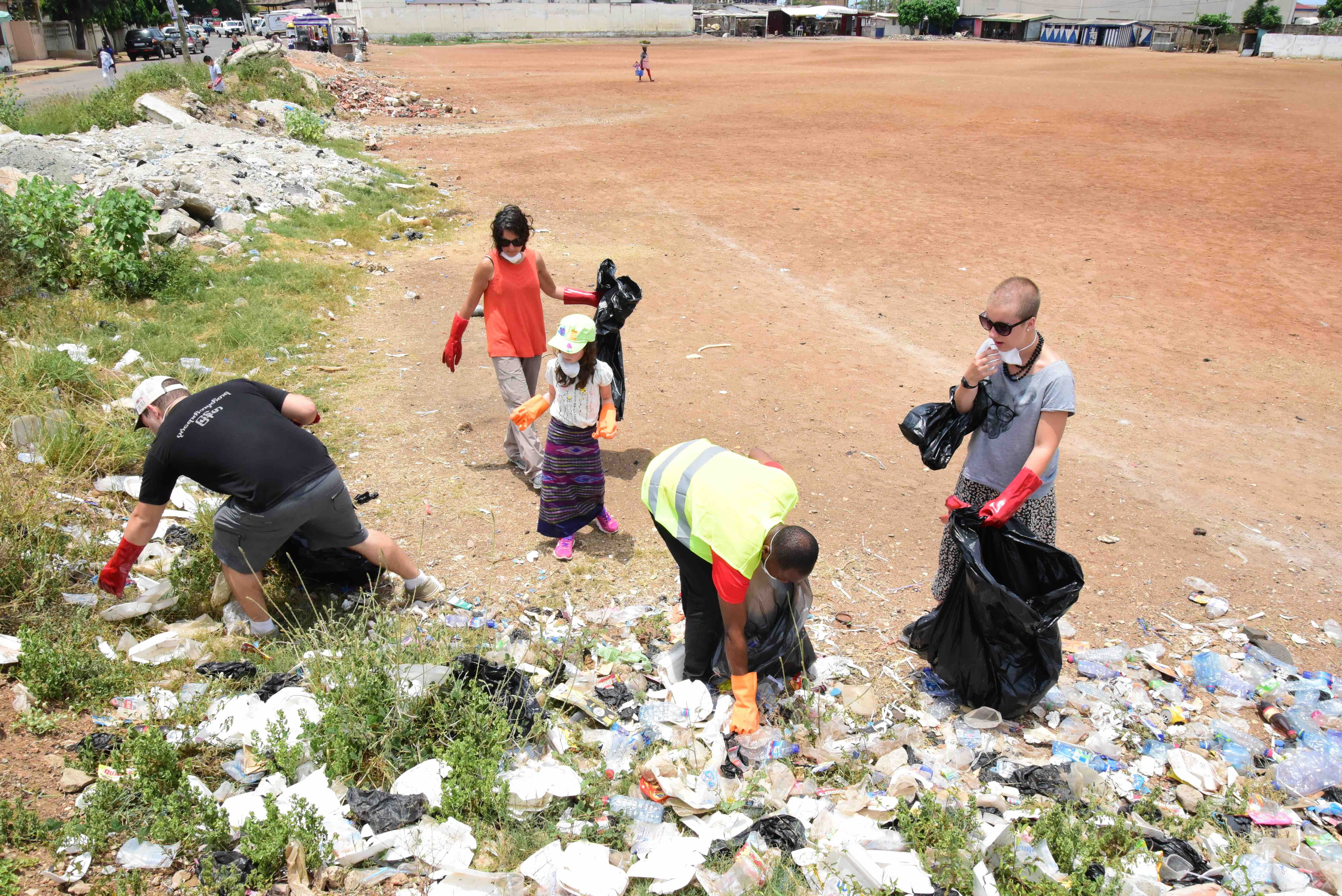 SAS students work to clean up a soccer field